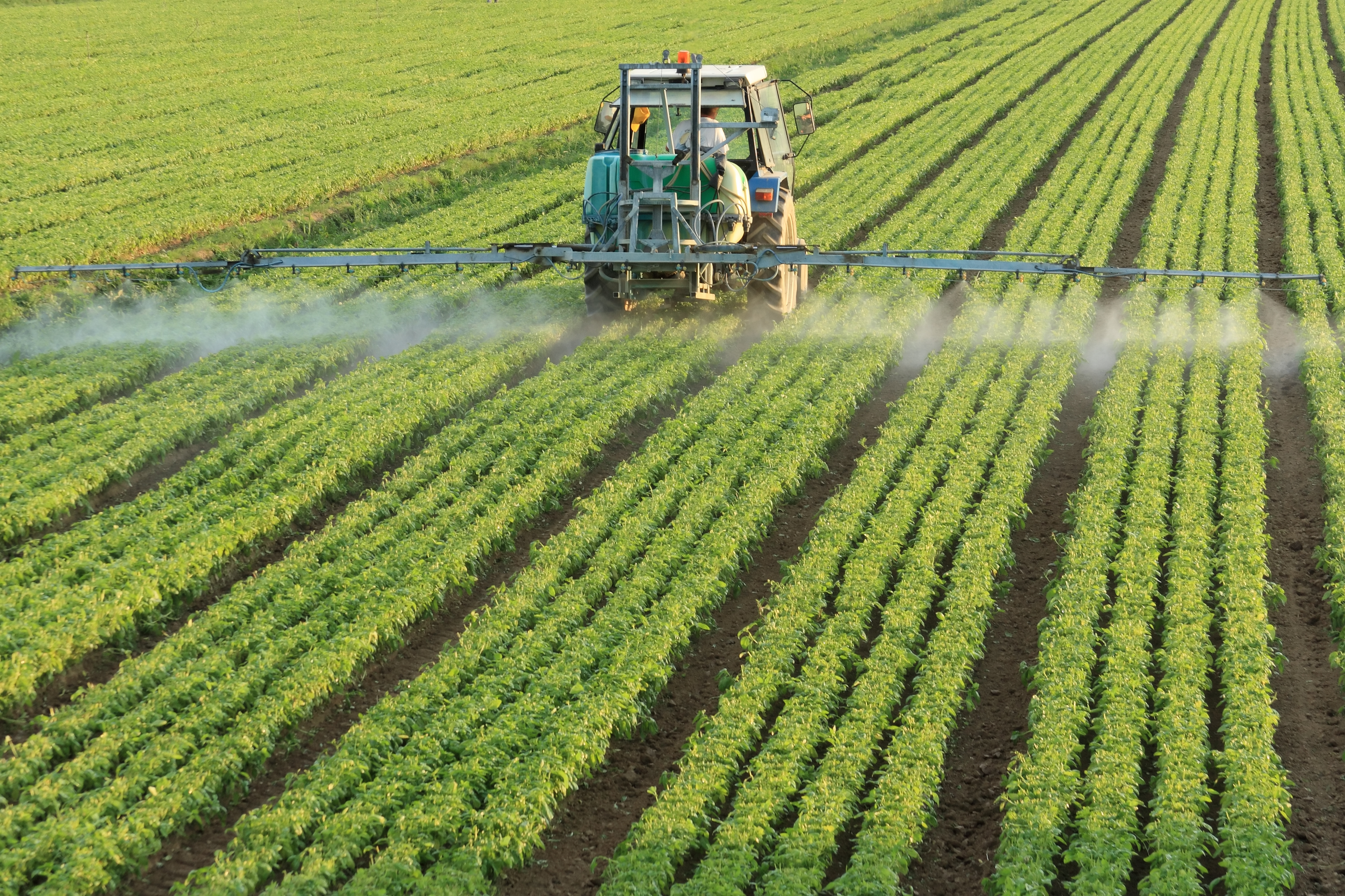 farming tractor spreading pesticides
