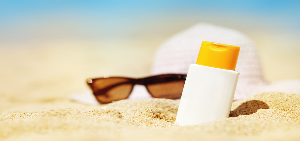 Bottle of sunscreen with shades on a beach