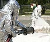 man in a full protective suit spraying a chemical