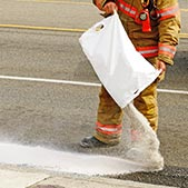Fireman pouring absorbent on oil spilled from a wreck