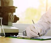 Chemist writing on clipboard while working in a laboratory