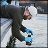 WVU researchers collect a water sample from the Elk River in Charleston, WV.