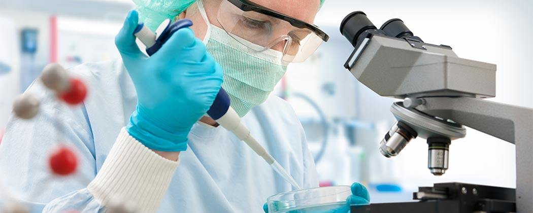 Scientist in safety gear examining a petri dish